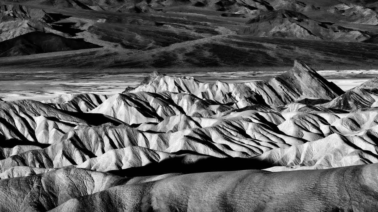 Black and white landscape photograph of Zabriskie Point in Death Valley, United States.