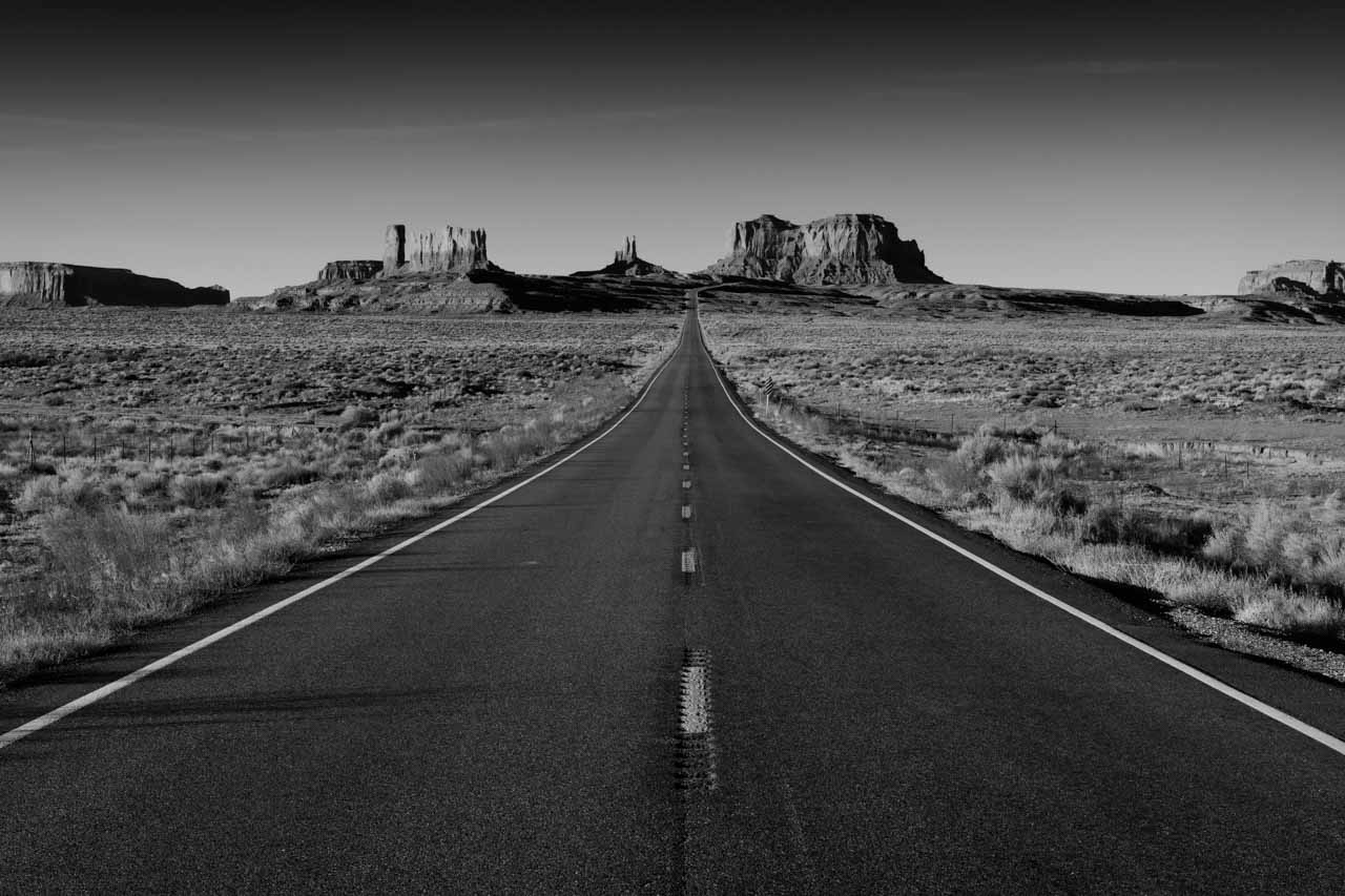 Photograph in black and white of a road to Monument Valley in Arizona. Photograph by Amar Guillen, photographer artist.