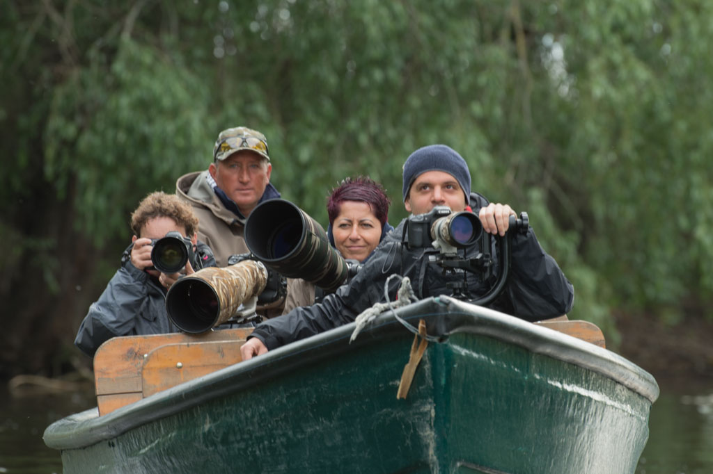In the Danube delta, photos are made from wooden boats. Three of the participants, Patricia, Agnes and Nicolas and their guide in an arm of the Danube.